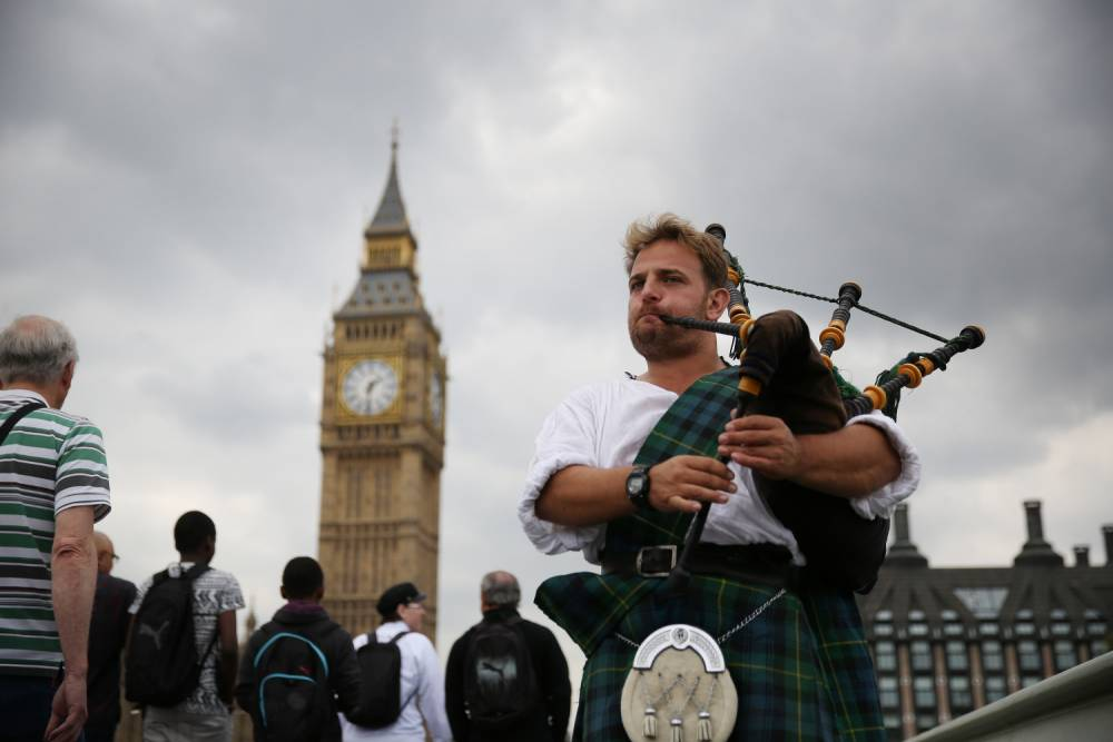 LONDON, ENGLAND - SEPTEMBER 10: Scotsman David Whitney plays the bagpipes on Westminster Bridge in sight of Parliament on September 10, 2014 in London, England. English councils and national government buildings have been asked to fly the Scottish Saltire flag. Scottish voters will take part in a referendum on September 18, 2014 to decide on independence. (Photo by Peter Macdiarmid/Getty Images)