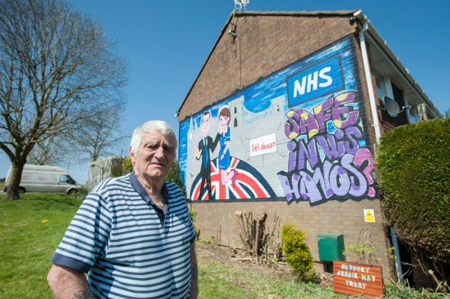 """A lifelong Labour voter has been told a 30ft graffiti mural of David Cameron throttling a nurse on the side of his house will have to go - because it breaches advertising rules. See SWNS story SWLABOUR; Retired Tony Davis (pictured) 73, is so passionate about politics he commissioned a local street artist to create the giant work on his end-of-terrace property. The mural, 30ft long and 10ft high, shows David Cameron with his hand around a nurse's throat, with the backdrop of Westminster and Clifton Suspension Bridge. A caption on the Patchway, Bristol, home reads: """"Safe in his hands?"""" before urging people to vote Labour."""