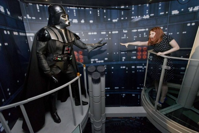 A member of staff poses with the wax figure of Star Wars character Darth Vader at the Star Wars At Madame Tussauds attraction in London on May 12, 2015. AFP PHOTO/JUSTIN TALLISJUSTIN TALLIS/AFP/Getty Images