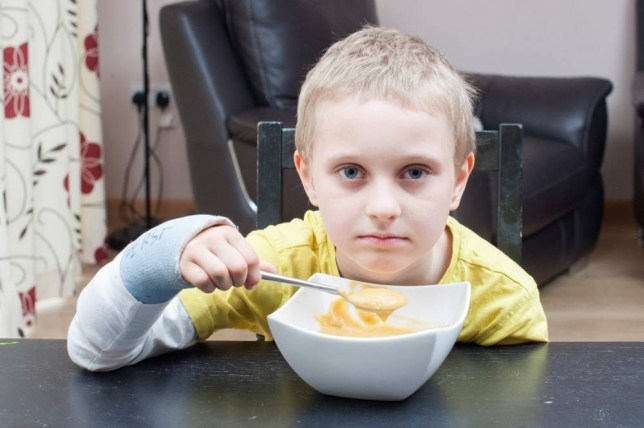 """Ocean Russell, 7, poses for a portrait at home in Severn Beach, England. May 19 2015. Russell will only eat liquid foods.  See SWNS story SWCHOKE; A """"skeletal"""" schoolboy with a rare phobia of choking is so afraid he can only eat Weetabix and SOUP. Ocean Russell, seven, started rejecting solid foods when he was four-years-old after his tonsils became swollen, giving him problems eating and sleeping. But his anxiety became so severe he is now only able to eat soft mushed up cereal, soup, liquidised baked beans and mashed potato - and only under the supervision of his mum. The little lad hasn't gained any weight in the last two years and refuses to eat at school, leaving his desperate mum Oxana, 36, worried about his future."""