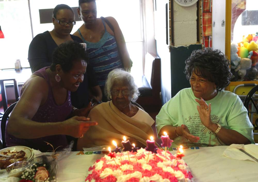 Jeralean Talley (C), the world's oldest-known living person, looks at the candles on her cake while family and friends sing 'Happy Birthday' during her 116th birthday celebration at a restaurant in Inkster, Michigan May 23, 2015.   REUTERS/Rebecca Cook