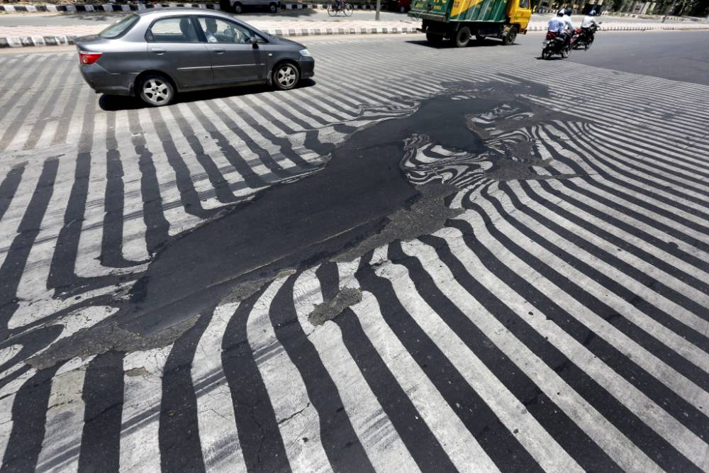 epa04769713 Road markings appear distorted as the asphalt starts to melt due to the high temperature in New Delhi, India, 27 May 2015. More than 1,150 people are reported dead from a heat wave sweeping across south India and Andhra Pradesh state was the worst hit, where 884 people had died of heatstroke since 18 May. Weather officials said northwesterly dry and hot winds from the desert state of Rajasthan were responsible.  EPA/HARISH TYAGI