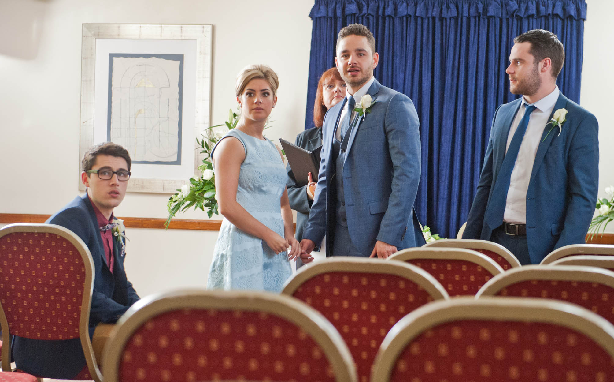 FROM ITV STRICT EMBARGO -TV Listings Magazines & websites Tuesday 16 June 2015, Newspapers Saturday 20 June 2015  Emmerdale - Ep 7217 Thursday 25 June 2015 - 1st Ep As Victoria Sugden [ISOBEL HODGINS] and Adam Barton [ADAM THOMAS] get ready for their wedding, both try hard not to think about the impending court case.  At the registry office, Aaron Livesy [DANNY MILLER] arrives and encourages a worried Adam not to worry and to just focus on himself and Victoria. Victoria arrives at her wedding accompanied by Finn Barton [JOE GILL]. It's all smiles for the intimate wedding party and the service begins. But the besotted pair and their two guests are soon distracted by a noise outside. Will an uninvited arrival halt proceedings?    Picture contact: david.crook@itv.com on 0161 952 6214 Photographer - Amy Brammall This photograph is (C) ITV Plc and can only be reproduced for editorial purposes directly in connection with the programme or event mentioned above, or ITV plc. Once made available by ITV plc Picture Desk, this photograph can be reproduced once only up until the transmission [TX] date and no reproduction fee will be charged. Any subsequent usage may incur a fee. This photograph must not be manipulated [excluding basic cropping] in a manner which alters the visual appearance of the person photographed deemed detrimental or inappropriate by ITV plc Picture Desk. This photograph must not be syndicated to any other company, publication or website, or permanently archived, without the express written permission of ITV Plc Picture Desk. Full Terms and conditions are available on the website www.itvpictures.com