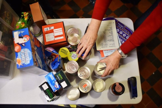 TO GO WITH AFP STORY BY JOE SINCLAIR A volunteer selects food for a visitor's order at a foodbank charity in west London on December 23, 2014. Food bank use in Britain is growing rapidly and Christmas has been a particularly busy time for centres like the one run by a Christian charity in the mostly affluent London neighbourhood of Fulham. Even as the British economy recovers from recession, many Britons are struggling to get by on low pay and reduced welfare, stirring a social unease that will be a key issue in the general election in May. AFP PHOTO / BEN STANSALL        (Photo credit should read BEN STANSALL/AFP/Getty Images)