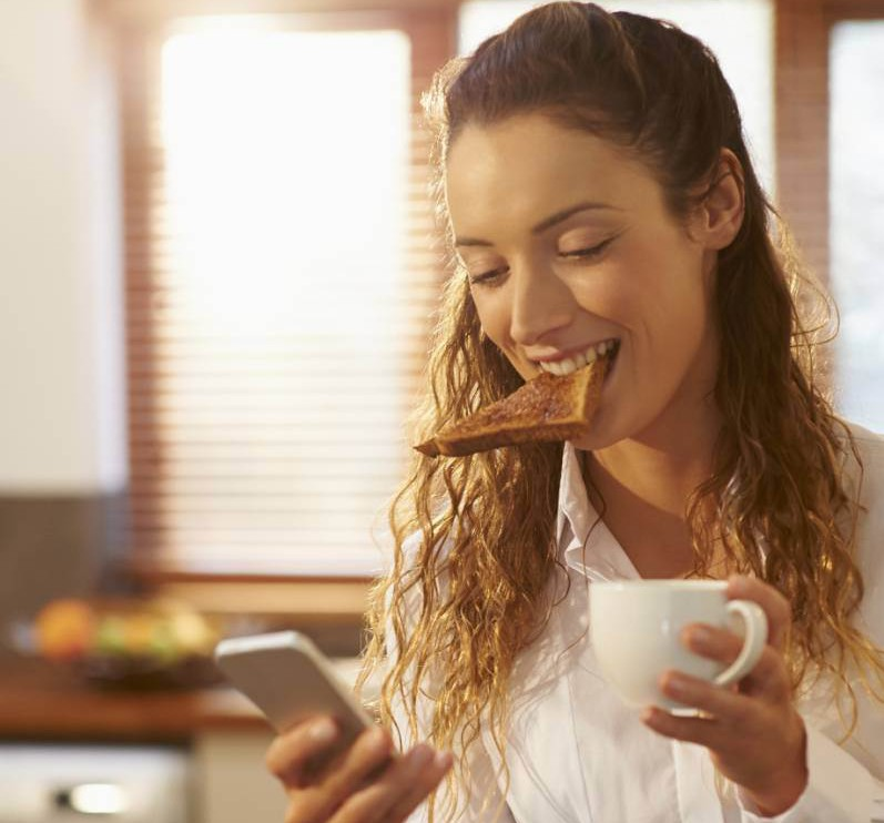 Woman eating breakfast and using phone at home.