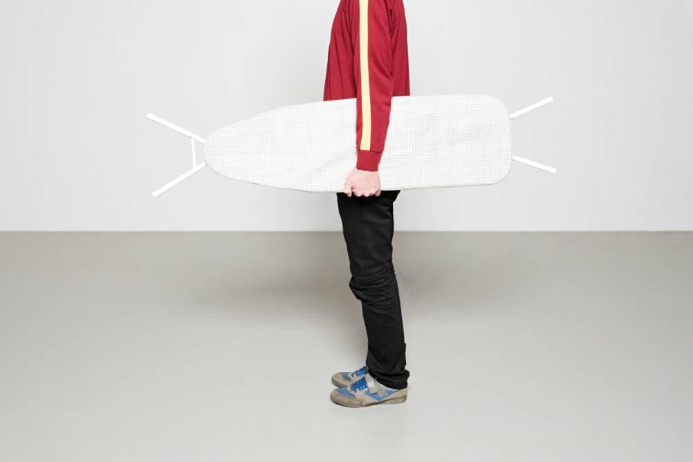 Man holding ironing board like surfboard