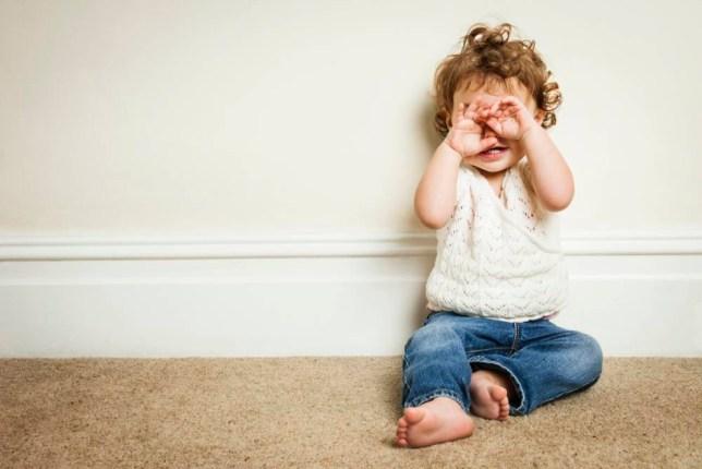 Young girl playing peekaboo through her hands.