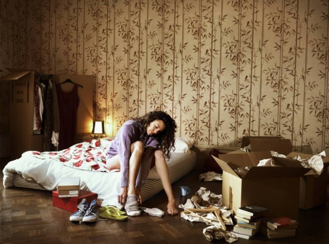 Woman sitting on bed by cardboard boxes, putting on socks