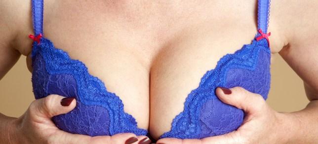 DK2M69 Woman adjusting her bra. Image shot 11/2013. Exact date unknown.