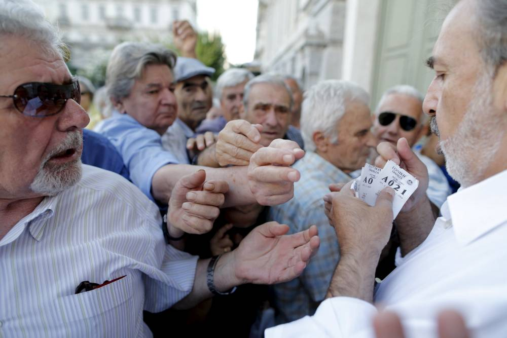 Pensioners are given priority tickets as they wait to receive part of their pensions at a National Bank branch in Athens, Greece, July 6, 2015. Greeks overwhelmingly rejected conditions of a rescue package from creditors on Sunday, throwing the future of the country's euro zone membership into further doubt and deepening a standoff with lenders. REUTERS/Christian Hartmann