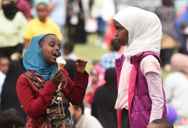 Ismahan Ali (left), aged nine enjoys an ice cream during Eid al-Fitr celebrations in Small Heath Park, Birmingham. PRESS ASSOCATION Photo. Picture date: Friday July 17, 2015. Eid al-Fitr marks the end of the holy month of Ramadan where Muslims fast during daylight hours. Photo credit should read: Joe Giddens/PA Wire