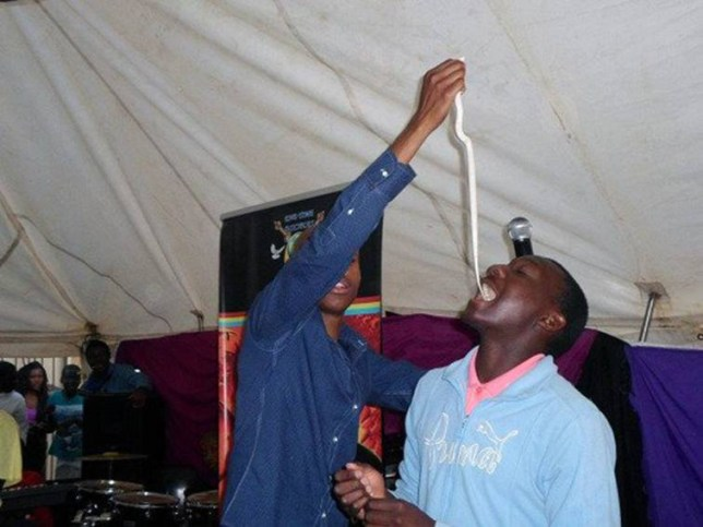 "Pic shows: One man eating a live snake.  A church congregation were controversially ordered to eat a live snake and told it would become and taste like chocolate. Members of Prophet Penuel's End Times Disciples Ministries in Soshanguve, Pretoria, in South Africa did as they were told and ate parts of the snake. Images posted onto the church's social media sites show radical preacher Penuel dangling a live snake and dropping it into the mouths of his followers. Members of the congregation posed showing chunks of the snake they had bitten of in their mouths.  After the strange event, a bizarre post on the churchís Facebook page read:""Man of God declared a snake to become a chocolate (chomp) and the congregation ate it. ""We have authority to change everything into anything and it will obey because of our authority,"" A member of the congregation said later on social media:""I did as I was commanded and tasted the chocolate. It was different but tasted good."" Another said:""I was not sure at first but when I bit the snake I realised it  was the best chocolate I have ever eaten."" The controversial Penuel previously commanded his church to drink petrol and eat cloths. (ends)"