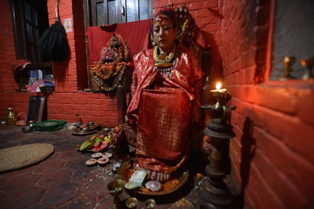 "TO GO WITH: Nepal-quake-religion-goddess, INTERVIEW by Paavan Mathema In this photograph taken on May 21, 2015, Dhana Kumari Bajracharya, the longest reigning Kumari of Nepal, sits in her quarters in Kathmandu. When a massive earthquake struck Nepal in April, the country's longest-reigning ""living goddess"", Dhana Kumari Bajracharya, left her quarters for the first time in three decades as tremors reduced nearby temples to rubble. AFP PHOTO / Ishara S. KODIKARAIshara S.KODIKARA/AFP/Getty Images"