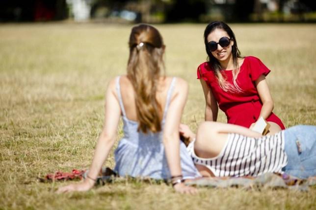Girls sitting down on grass enjoying the sun