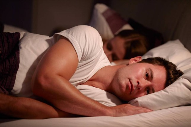 EMDDGJ Man Lying Awake In Bed Suffering With Insomnia