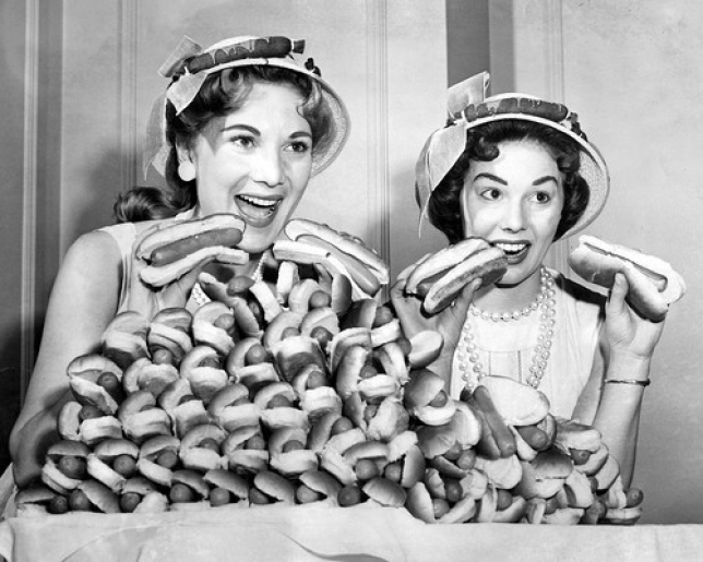 Black and white shot of women eating hot dogs