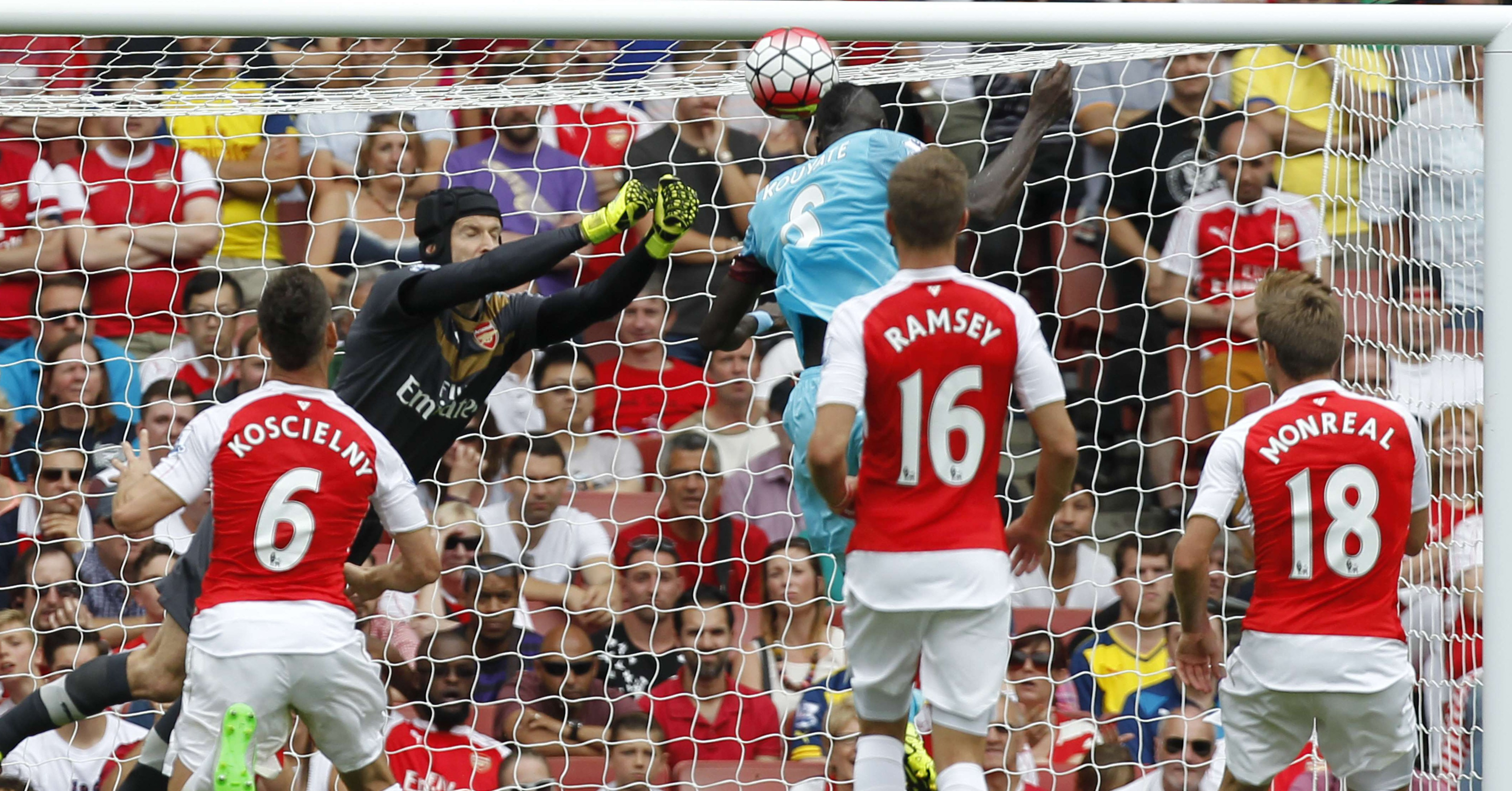 """West Ham United's Senegalese midfielder Cheikhou Kouyate (3rd R) heads past Arsenal's Czech goalkeeper Petr Cech for the opening goal of the English Premier League football match between Arsenal and West Ham United at the Emirates Stadium in London on August 9, 2015. AFP PHOTO / IKIMAGES RESTRICTED TO EDITORIAL USE. No use with unauthorised audio, video, data, fixture lists, club/league logos or """"live"""" services. Online in-match use limited to 45 images, no video emulation. No use in betting, games or single club/league/player publications.IKIMAGES/AFP/Getty Images"""