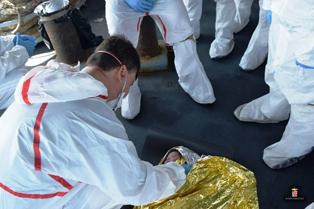 """A handout picture released by the Italian navy press office Marina Militaire shows crew of the Italian navy destroyer Mimbelli gathering around a baby rescued from the site where a boat carrying over 600 migrants capsized in the Mediterranean off the Libyan coast on August 5, 2015. Survivors of a shipwreck off the coast of Libya in which some 200 migrants were feared drowned were being brought to safety in Sicily on August 6, as tales emerged of the 'horrific' moment the boat overturned. AFP PHOTO / MARINA MILITARE == RESTRICTED TO EDITORIAL USE - MANDATORY CREDIT """"AFP PHOTO / MARINA MILITARE"""" - NO MARKETING NO ADVERTISING CAMPAIGNS - DISTRIBUTED AS A SERVICE TO CLIENTS ==MARINA MILITARE/AFP/Getty Images"""