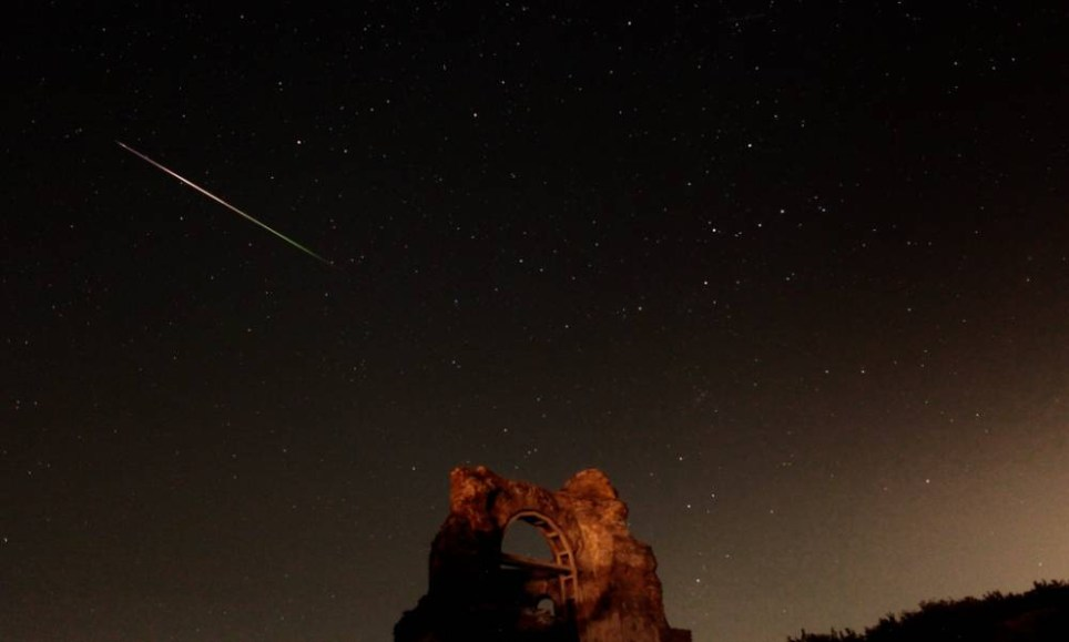 epaselect epa04881637 A long exposure image showing a meteor streaking across the night sky over the ruins of the early Byzantine Christian basilica 'Red Church', dating to the late 4th and 5th century near the town of Perushtitsa some 120 km from Sofia, Bulgaria, 13 August 2015. The meteor display, known as the Perseid shower, because it appears to radiate from the constellation Perseus in the northeastern sky, is a result of Earth's orbit passing through debris from the comet Swift-Tuttle. This weekend is considered the peak of the shower, which is visible every August. EPA/VASSIL DONEV