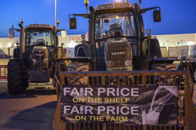 16 Aug 2015, Severn Beach, Gloucestershire, England, UK --- Severn beach, United Kingdom. 16th August 2015 -- Tractors in front of the Tesco distribution depot in Avonmouth protesting about imported dairy products Tesco use instead of British dairy products. -- Dairy farmers led by Farmers For Action Chairman, David Handley, blockaded both Tesco's and farmfoods distribution depots in Avonmouth near Bristol. They are protesting about the cheap price of milk paid by farmfoods and imported milk used by Tesco. --- Image by © Michael Scott/Demotix/Corbis