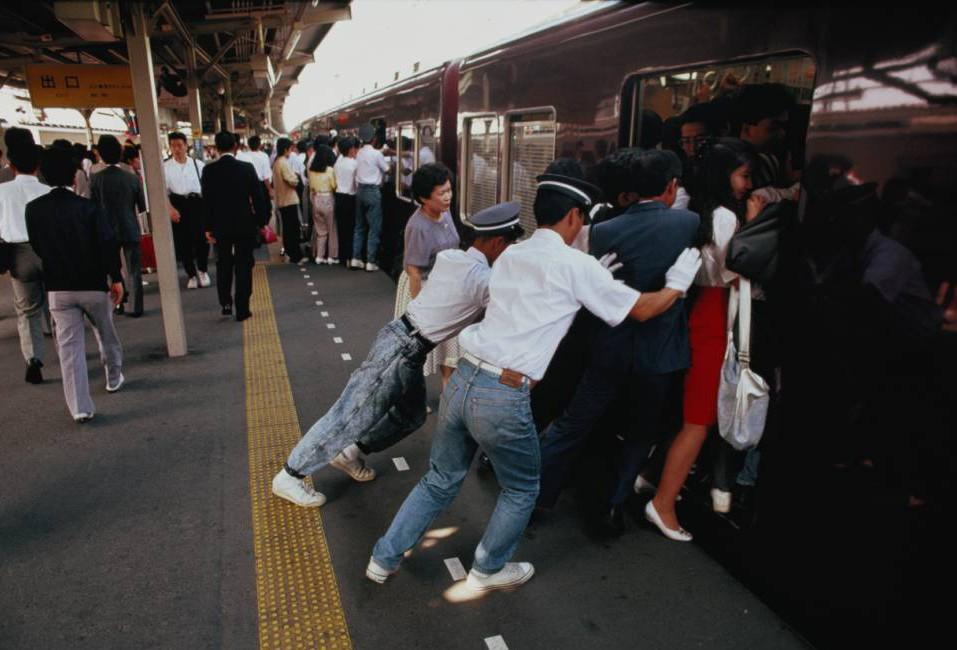 Japan, Honshu, Tokyo, railway staff squeezing commuters onto train