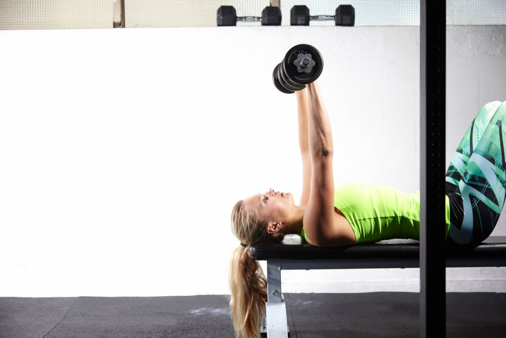 Young female crossfitter lying on training bench lifting bar bell in gym