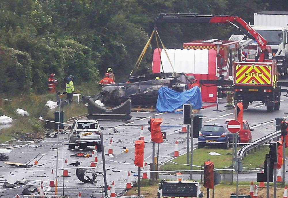 SHOREHAM, ENGLAND - AUGUST 25: A large piece on the crashed Hawker Hunter fighter jet is lifted by crane (top) on August 25, 2015 in Shoreham, England. The aircraft came down while performing at the Shoreham Airshow on August 22nd. Police say that the death toll remains at 11 after the removal of parts of the wreckage yesterday. (Photo by Peter Macdiarmid/Getty Images)
