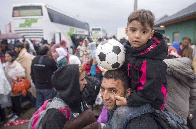 Migrants arrive on the Hungarian-Austrian border near Nickelsdorf in early hours on September 5, 2015, from where they wish to head to Salzburg on the German-Austrian border. The first bus carrying migrants who have been stranded in the Hungarian capital reached the Austrian border early September 5, after Vienna and Berlin agreed to take in thousands of refugees desperate to start new lives in Western Europe. Some 2,500-3,000 migrants have entered Austria from Hungary in the past few hours, Austrian police said early September 5. AFP PHOTO/JOE KLAMARJOE KLAMAR/AFP/Getty Images