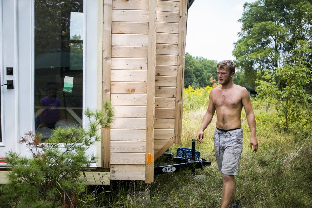 "In this Wednesday, Sept. 2, 2015 photo, Christopher Cerk installs his tiny house, which he built by hand, in Ann Arbor, Mich. Cerk, 21, says, ""Around freshman year I didn't enjoy living in the dorms so I wanted to do something different. I started researching different ways to live. I wanted to put all the money that would be going towards rent ... to something else."" (Dominic Valente/The Ann Arbor News via AP)"