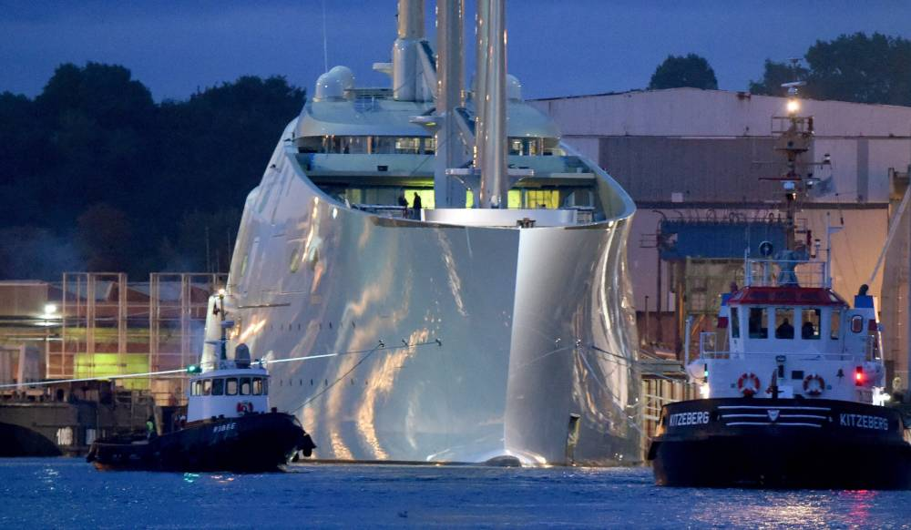 epa04942077 The sailing ship 'White Pearl', described by media as a 'Mega sailing yacht', is tugged from a port basin as it is prepared for a test voyage in Kiel, norther Germany, 21 September 2015 morning. The sailing ship with masts of up to 90 meters has been built by the 'German Naval Yards' ship builders. According to media reports it is believed that the yacht was ordered and is owned by Russian multi billionaire Andrey Igorevich Melnichenko. EPA/CARSTEN REHDER
