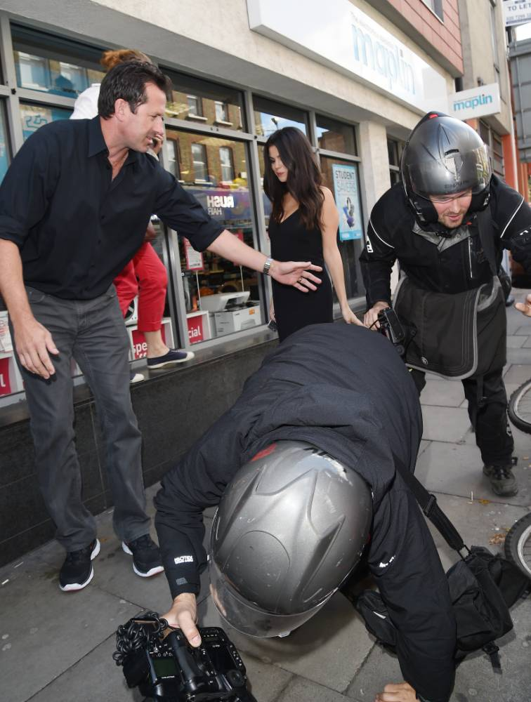 Karma strikes! Clumsy photographer takes a tumble trying to snap Selena Gomez. She laughs