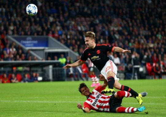 PSV's Hector Moreno, down, tackles Manchester Unitedís Luke Shaw, up, during the Champions League Group B soccer match between PSV and Manchester United at Philips stadium in Eindhoven, Netherlands, Tuesday, Sept. 15, 2015. (AP Photo/Peter Dejong)