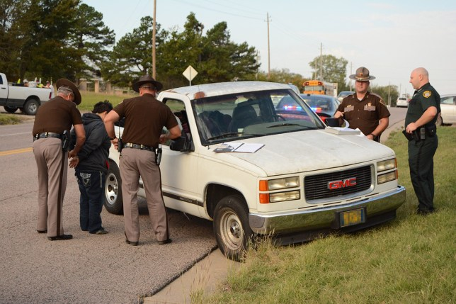 In this photo taken Wednesday, Oct. 21, 2015, Oklahoma Highway Patrol troopers Keith Teel, left, and Brian Bagwell arrest a woman on suspicion of driving under the influence after she allegedly fell out of a moving pickup truck in Ada, Okla. Authorities say a 3-year-old boy took the wheel of the pickup truck and drove it several blocks across four lanes of an Oklahoma highway after his apparently intoxicated mother fell out. (Randy Mitchell/The Ada News via AP) MANDATORY CREDIT