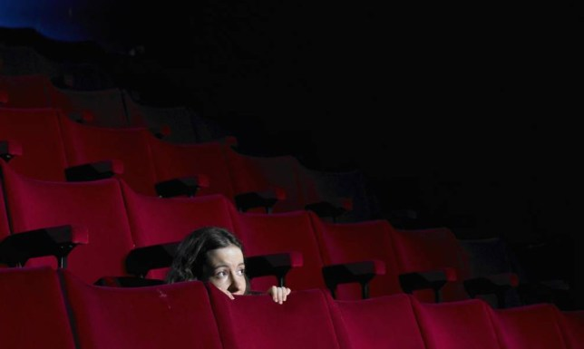 Young woman hiding behind seat in empty cinema
