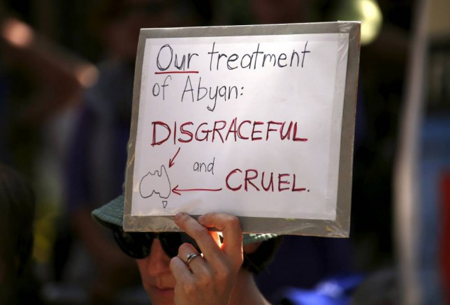 A protester holds a placard during a rally in support of refugees in central Sydney, Australia, October 19, 2015. Australia launched its candidacy for the United Nations Human Rights Council on Monday, but the bid was overshadowed by a bitter dispute between the government and human rights lawyers over the fate of a pregnant Somali asylum seeker who claims she was raped. Immigration Minister Peter Dutton accused refugee advocates and lawyers of fabricating stories about the treatment of the 23-year-old woman, known as Abyan, while refugee advocates have likened her removal from Australia in the dead of night to rendition. The dispute has again thrown the spotlight on Australia's controversial immigration policies, which include turning back boats of refugees at sea and holding asylum seekers in offshore detention camps in poor Pacific island nations. REUTERS/David Gray