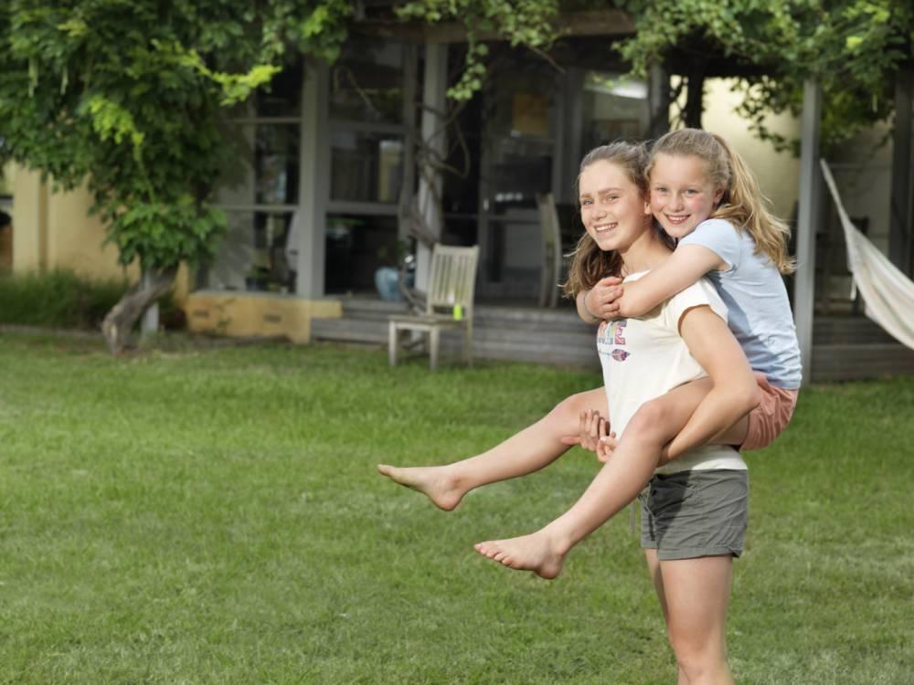 Teenage girl giving her sister piggyback ride in garden