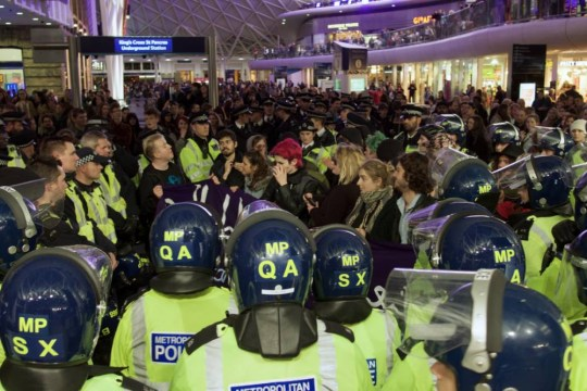 """24 Oct 2015, London, England, UK --- London, United Kingdom. 24th October 2015 -- Dozens of police surround and """"kettle"""" a small group of protesters who have entered King's Cross station calling for the elimination of national borders. -- With chants of """"No Borders"""" and """"No Humans Are Illegal"""", protesters were met by a huge police presence at the St Pancras Eurostar terminal. Despite some clashes, a group of women reached the arrival zone and unveiled a large banner. --- Image by © indy rikki/Demotix/Corbis"""