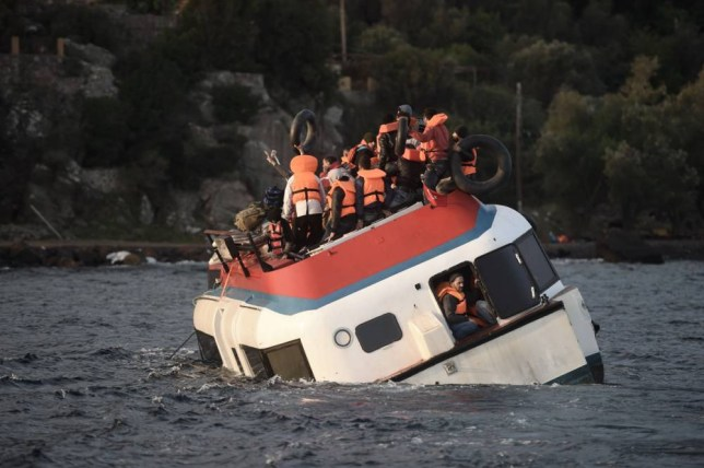 Refugees and migrants call for help as their boat sinks off the Greek island of Lesbos after crossing the Aegean sea from Turkey on October 30, 2015. AFP PHOTO / ARIS MESSINISARIS MESSINIS/AFP/Getty Images