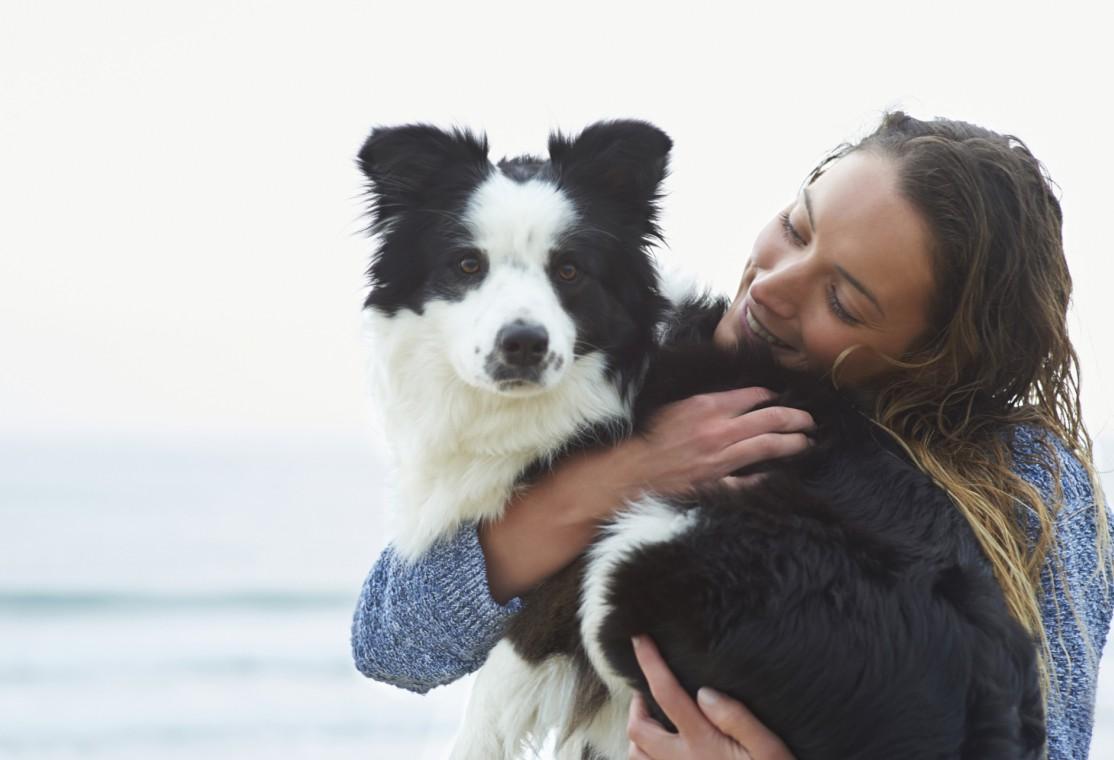 Woman hugging dog beside sea.