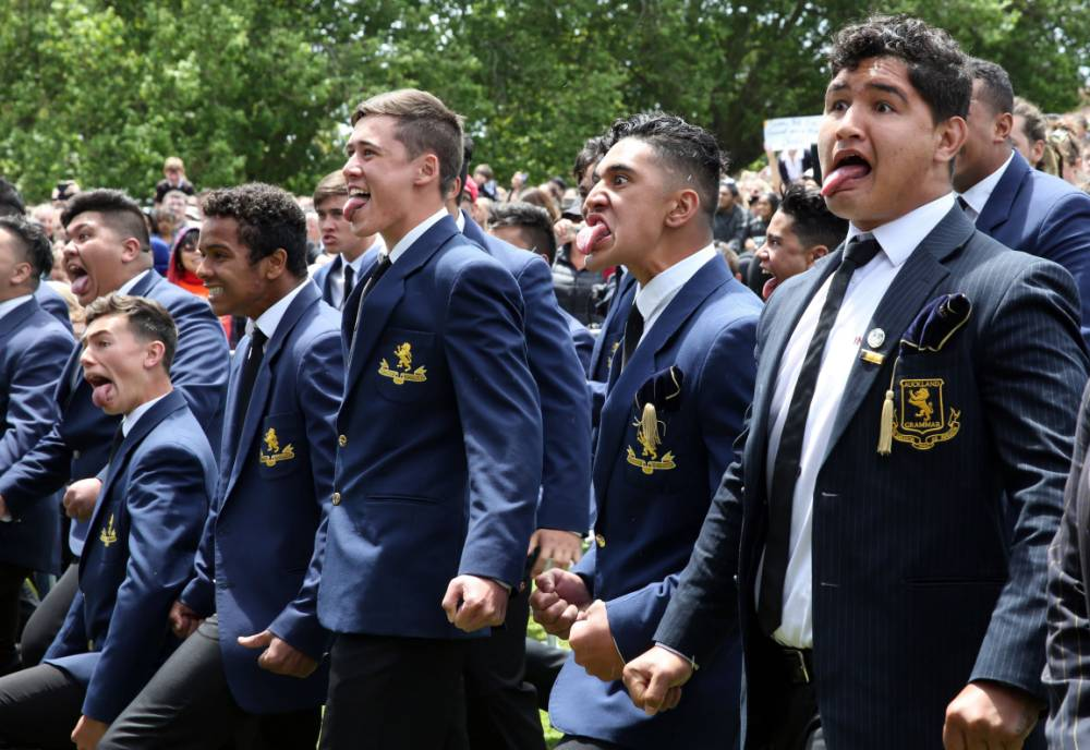 Airport ground staff and students perform a haka for New Zealand's All Blacks after their arrival in Auckland