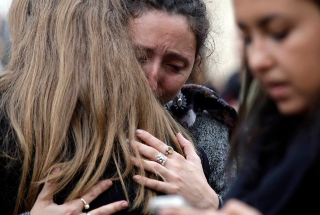 People hug each other as they gather in front of the French embassy in Rome, Saturday, Nov. 14, 2015. French police on Saturday hunted possible accomplices of eight assailants who terrorized Paris concert-goers, cafe diners and soccer fans with a coordinated string of suicide bombings and shootings in France's deadliest peacetime attacks. (AP Photo/Gregorio Borgia)