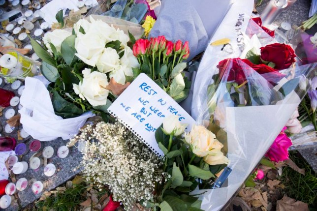 epa05026172 Flowers and candles lay at the memorial set near the Bataclan concert venue in Paris, France, 15 November 2015. More than 120 people have been killed in a series of attacks in Paris on 13 November, according to French officials. Eight assailants were killed, seven when they detonated their explosive belts, and one when he was shot by officers, police said. French President Francois Hollande says that the attacks in Paris were an 'act of war' carried out by the Islamic State extremist group. EPA/JULIEN WARNAND