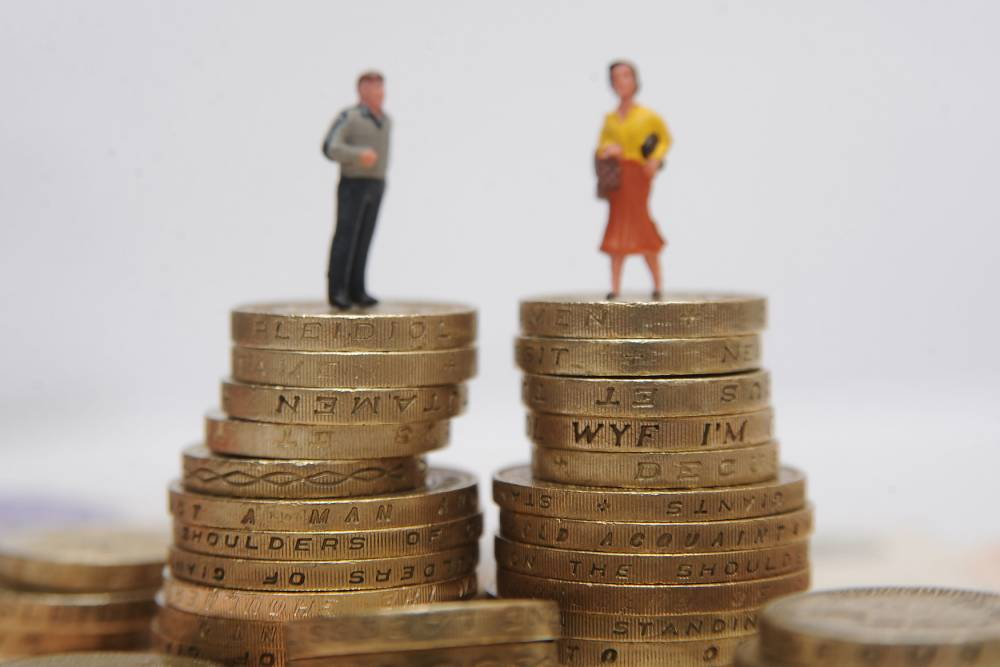 File photo dated 11/8/2014 of plastic models of a man and woman standing on a pile of coins, as the gender pay gap has fallen slightly to 9.4%, the lowest since 1997, but little has changed for the past four years, figures have shown. PRESS ASSOCIATION Photo. Issue date: Wednesday November 18, 2015. The difference between the median earnings of full-time men and women workers fell by 0.2% compared with last year. See PA story INDUSTRY Pay. Photo credit should read: Philip Toscano/PA Wire
