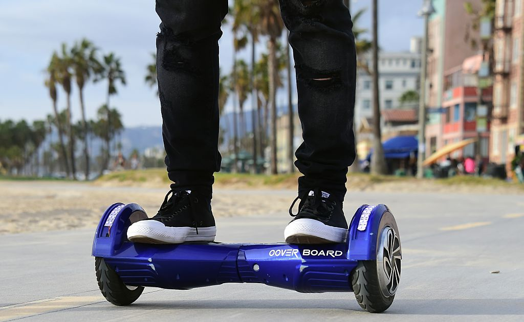 """Michael Tran uses his hoverboard on the Venice Beach Boardwalk on December 10, 2015. The hot item on many holiday lists will help you zip around town, the shopping mall and from one end of the workplace to another.These so-called """"hoverboards"""" or self-balancing electric scooters, are surging in popularity in the first season where they have been available at relatively affordable prices -- as low as $300 for some models. AFP PHOTO/ FREDERIC J. BROWN / AFP / FREDERIC J. BROWN (Photo credit should read FREDERIC J. BROWN/AFP/Getty Images)"""