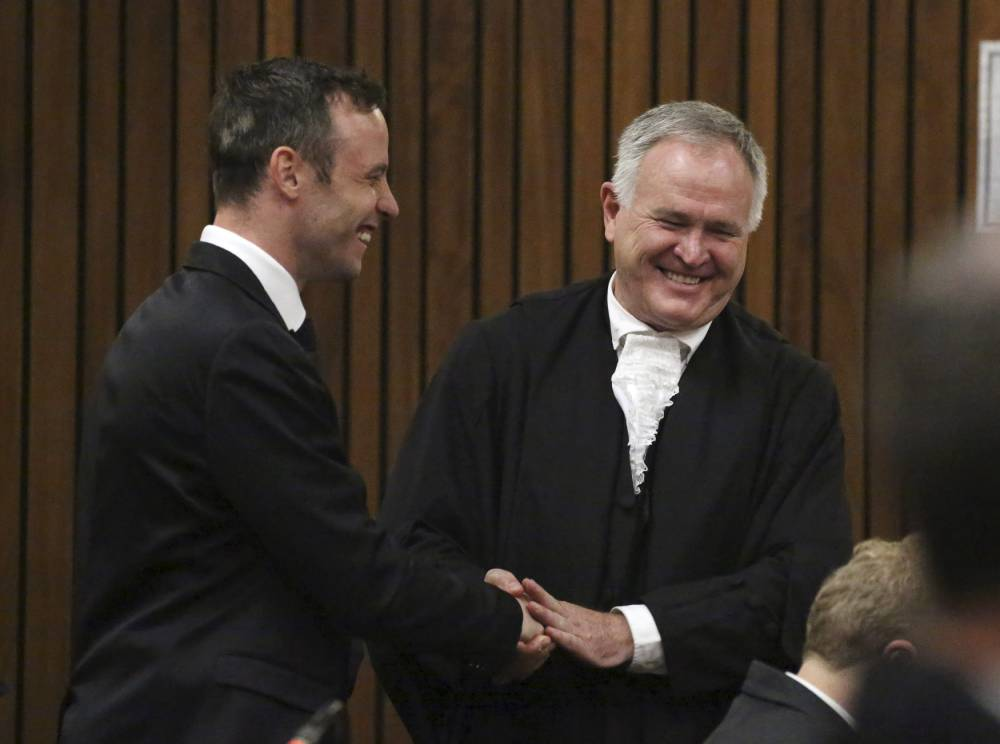 Oscar Pistorius (L) speaks with his defence advocate Barry Roux in the dock at the North Gauteng High Court in Pretoria, South Africa for a bail hearing, December 8, 2015. REUTERS/Siphiwe Sibeko
