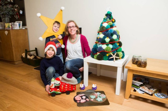 "Jen Gale and her sons William, 7, and Samuel, 4, who have made various homemade Christmas decorations. Warminster, Wiltshire. See SWNS story SWCRAFT: A thrifty mum has revealed why she won't be buying her children any toys for Christmas - but will MAKE all of their presents instead. Mum-of-two Jen Gale, 38, will wrap up homemade bath bombs and bobble hats for her two young boys - instead of giving them the Star Wars toys and Lego that they asked for. She plans to spend less than £30 on making quirky presents for sons William, seven, and Samuel, four, because she is fed up with today's ""disposable society"", she said. The Gales will also send homemade cards and eat their Turkey dinner at a table covered in hand-crafted decorations - next to a DIY Christmas tree fashioned from pom poms."