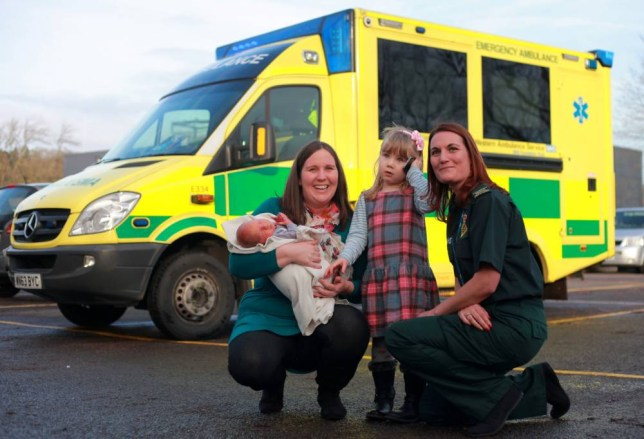 """Catherine Bazzard with her daughter Emma who saved her mum's life when she dialled 999 to report that her she had fallen down the stairs. Also pictured is the family's new arrival George and paramedic Sarah Morris. See SWNS story SWCALL: An adorable three-year-old girl is getting a bravery award today (wed) for the endearing 999 call she made to save her pregnant mum's life. Little Emma picked up the phone after finding her heavily-pregnant mum Catherine unconscious at the bottom of the stairs. She dialled 999 and calmly gave her address and told the operator her mum had fallen down the stairs with """"a baby in her tummy"""". She stayed on the line for 11 minutes, explained her mum had banged her head but was not bleeding and said she had even checked the door was unlocked ready for an ambulance crew."""