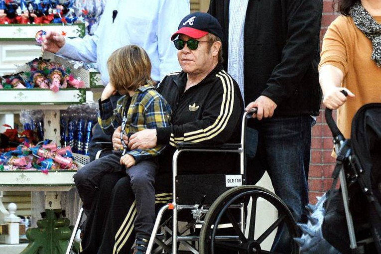 Elton John was spotted enjoying a day at Disneyland with his two kids and husband David Furnish. The legendary singer was seen with his son Zachary on his lap and being wheeled around in a wheelchair with the help of a bodyguard. <P> Pictured: Elton John, Zachary Jackson Levon Furnish-John <B>Ref: SPL1198924 231215 </B><BR /> Picture by: Sharpshooter Images /Splash<BR /> </P><P> <B>Splash News and Pictures</B><BR /> Los Angeles: 310-821-2666<BR /> New York: 212-619-2666<BR /> London: 870-934-2666<BR /> photodesk@splashnews.com<BR /> </P>