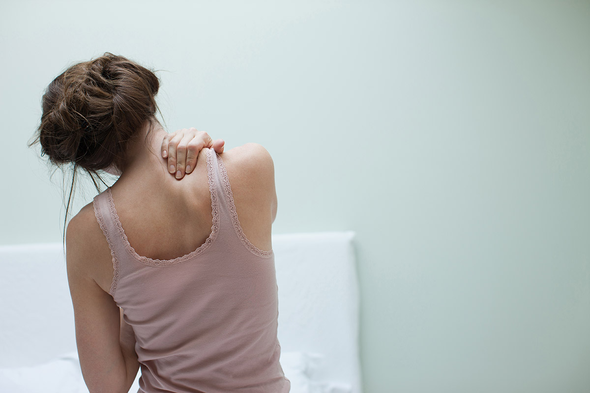 Woman rubbing aching back Getty