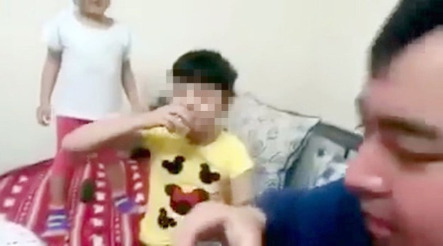 """Pic shows: The father and his two daughter drinking vodka. Internet users in Kazakhstan have been shocked by a video of a dipso-dad teaching his five.-year-old toddlers to guzzle VODKA. Vodka - the white grain spirit blamed for much of the violence, road accidents and suicides that afflicts the country and its larger neighbour Russia - can be up to 100 percent proof. The bizarre incident was footaged somewhere in Kazakhstan. The video shows the man sitting at a table pouring vodka into shot glasses. The father calls his daughters """"drunkies"""" and is clearly excited about the idea of them drinking vodka. The man is seen giving a shot to one girl. He raises his glass in a cheers motion and gives her a snack to eat after she has downed the fiery liquour. After that the second girl asks her dad for a drink. Looking drunkenly pleased with himselof, he pours out a tot for her too. A woman in the background, probably the camerawoman, is heard laughing heartily. While it is unclear if the daughters were drinking vodka - or if it was water in the vodka bottle - the grimace that they make after downing the drink tends to lend weight to the theory that it was the real thing. Police are now involved in trying to trace the drunken dad. The majority of Internet commentators were enraged by the action of the girlsí parents and criticized them mercilessly. But there were some who thought that he was giving them medicine instead. Until the police track him down the issue remains unsolved. If he was indeed encouraging them to drink vodka he could face a heavy fine and authorities could even remove the children to a safer environment. (ends)"""